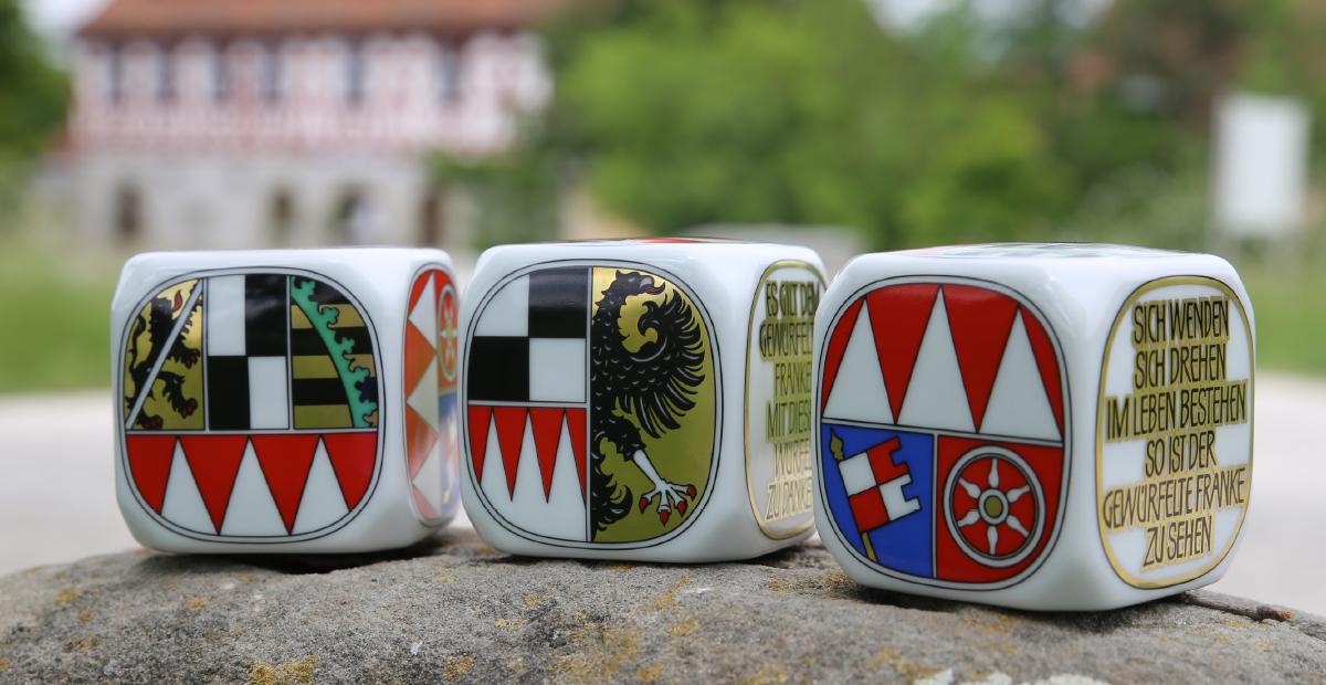 Das Foto zeigt drei Frankenwürfel mit der Seite des jeweiligen Regierungsbezirks